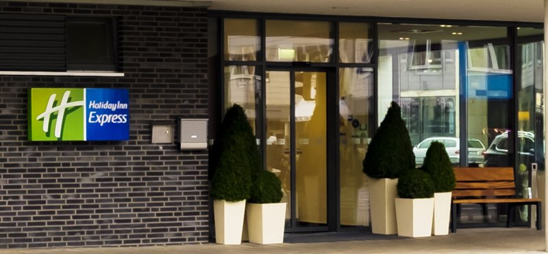 Holiday Inn Express Guetersloh-The hotel entrance with plants and a wooden bank.<br/>Image from Leonardo