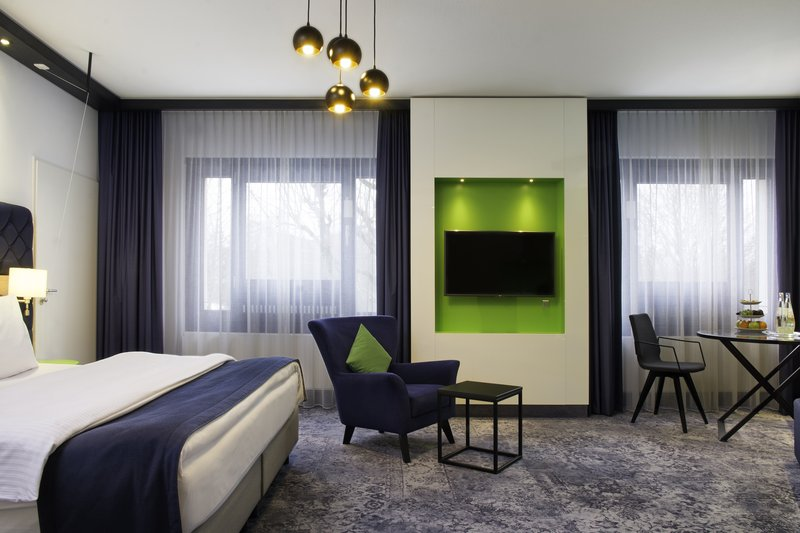 Holiday Inn Stuttgart-A spacious accessible room with a king bed and a sitting area.<br/>Image from Leonardo
