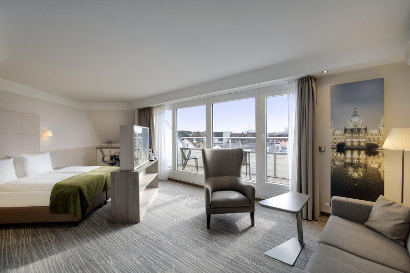 Crowne Plaza Hannover-An executive room with a separate seating area and a balcony.<br/>Image from Leonardo