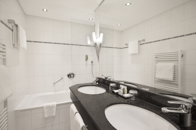Crowne Plaza Hannover-A bright bathroom with a soaking tub and his and hers sinks.<br/>Image from Leonardo