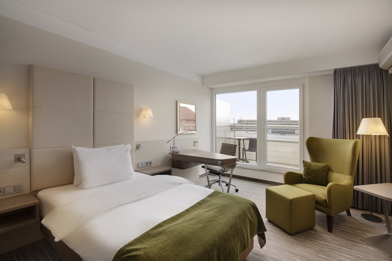 Crowne Plaza Hannover-A view to the balcony from a Crowne Plaza room with a single bed.<br/>Image from Leonardo