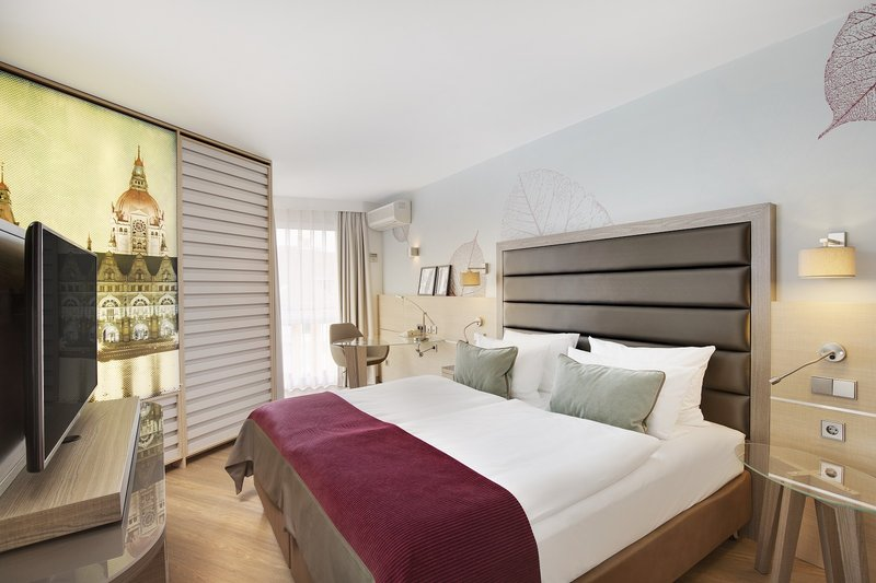 Crowne Plaza Hannover-An executive room with a king bed and a wall photo of Hannover.<br/>Image from Leonardo