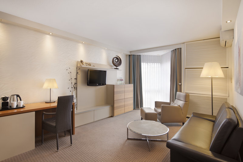 Crowne Plaza Hannover-A suite living room with extra seating and flat-screen TV.<br/>Image from Leonardo