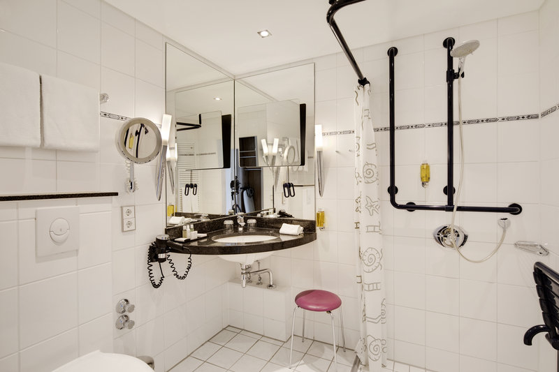 Crowne Plaza Hannover-An accessible bathroom with grab bars and a shower seat.<br/>Image from Leonardo