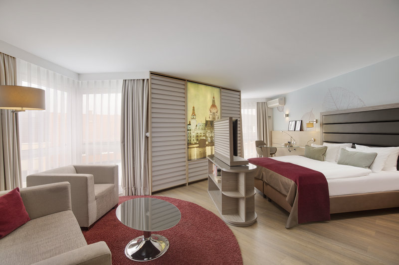 Crowne Plaza Hannover-An executive room with a flat-screen TV and separate seating area.<br/>Image from Leonardo