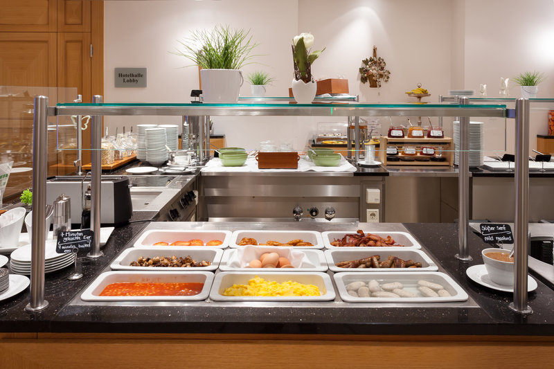 Holiday Inn Nuernberg City Centre-Hot dishes including eggs and sausage at the breakfast buffet.<br/>Image from Leonardo