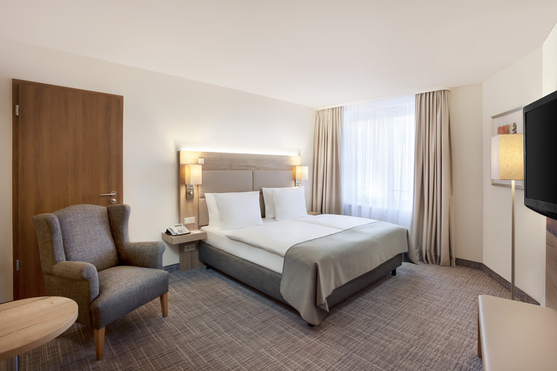 Holiday Inn Nuernberg City Centre-A double room in warm tones, with a comfortable armchair.<br/>Image from Leonardo