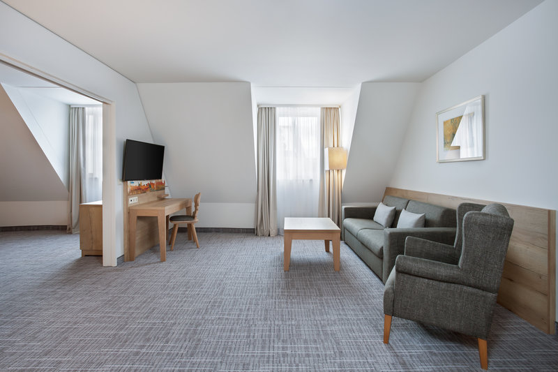 Holiday Inn Nuernberg City Centre-Spacious living room in a suite, with a sofa, chair and work desk.<br/>Image from Leonardo