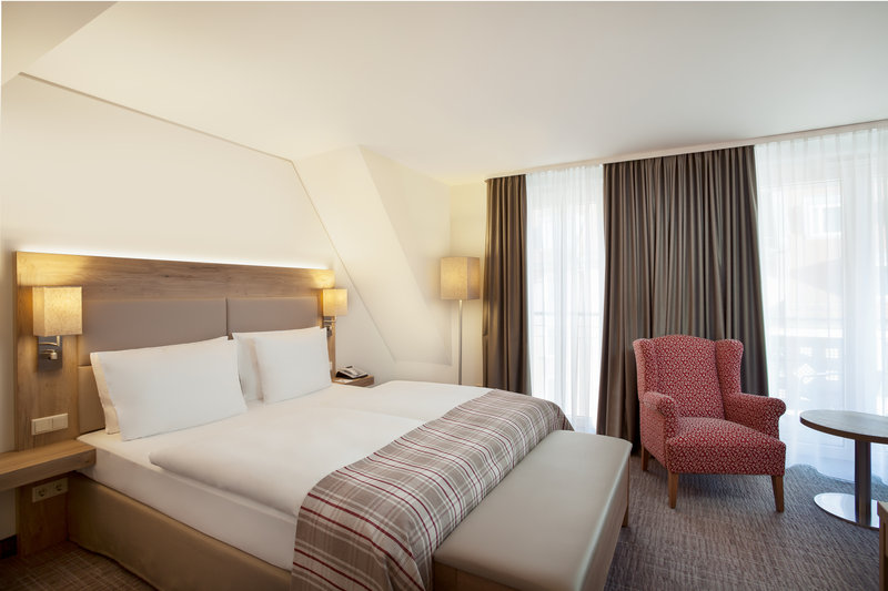 Holiday Inn Nuernberg City Centre-Double bed in a family room, with blackout blinds and an armchair.<br/>Image from Leonardo