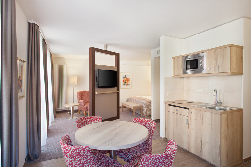 Holiday Inn Nuernberg City Centre-Large family room with a kitchenette, dining table and chairs.<br/>Image from Leonardo