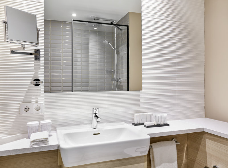 Crowne Plaza Hamburg - City Alst-New designed bright bathroom with wood accents and rain shower.<br/>Image from Leonardo