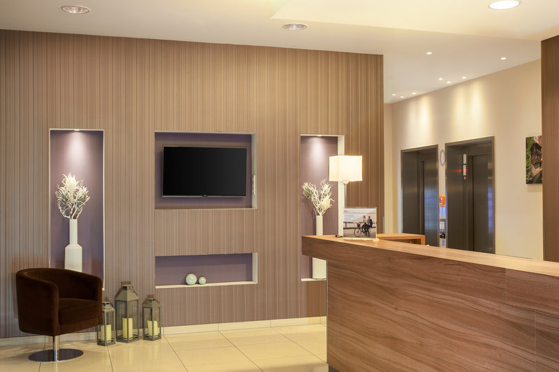 Holiday Inn Express Nuremberg City - Hauptbahnhof-Well-lit hotel lobby with TV and front desk<br/>Image from Leonardo