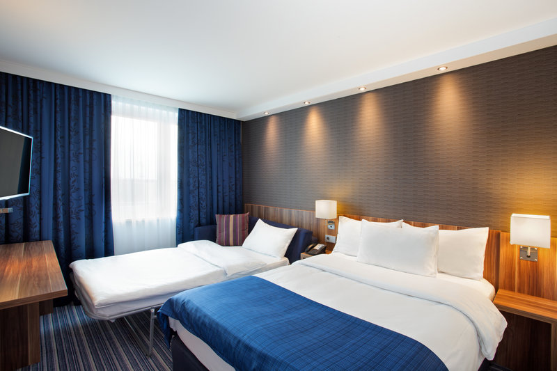 Holiday Inn Express Nuremberg City - Hauptbahnhof-A family room with a sofa bed set up ready for guests.<br/>Image from Leonardo