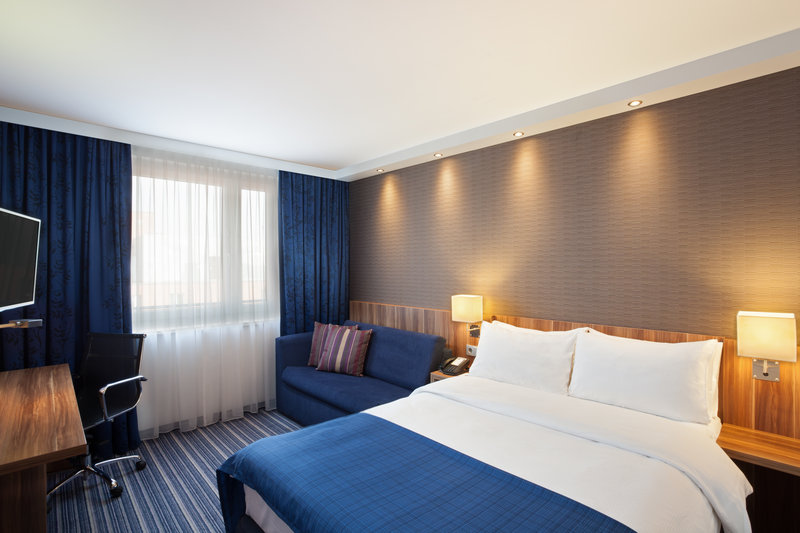 Holiday Inn Express Nuremberg City - Hauptbahnhof-Handsomely appointed bedroom with a sofa and a work desk.<br/>Image from Leonardo