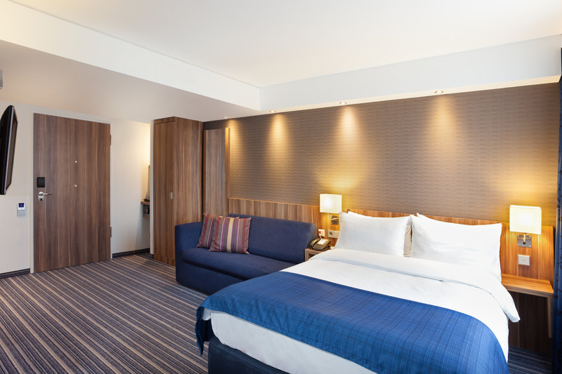 Holiday Inn Express Nuremberg City - Hauptbahnhof-A warmly decorated bedroom with a comfortable sitting area. <br/>Image from Leonardo