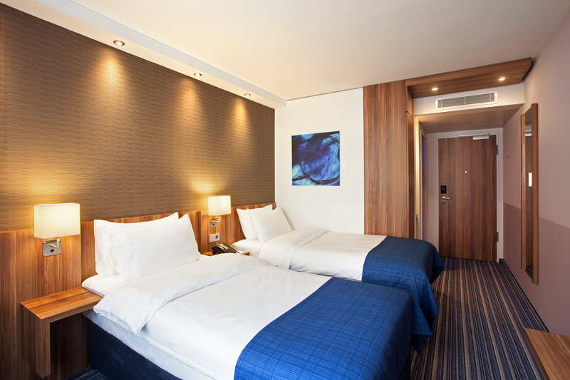 Holiday Inn Express Nuremberg City - Hauptbahnhof-An inviting bedroom with soothing neutral tones and a pillow menu.<br/>Image from Leonardo