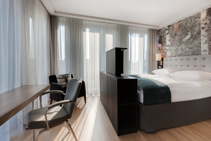 Holiday Inn Berlin Centre Alexanderplatz-A spacious accessible room with large windows and a work desk.<br/>Image from Leonardo