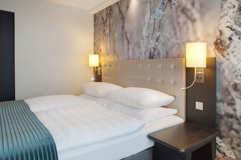 Holiday Inn Berlin Centre Alexanderplatz-A queen-size bed with a padded headboard.<br/>Image from Leonardo