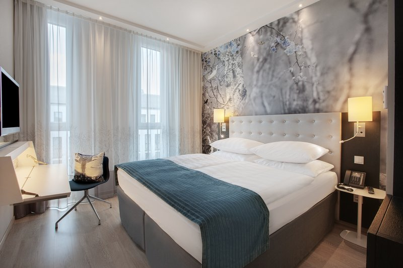 Holiday Inn Berlin Centre Alexanderplatz-Airy Deluxe King room with large work desk and padded headboards.<br/>Image from Leonardo