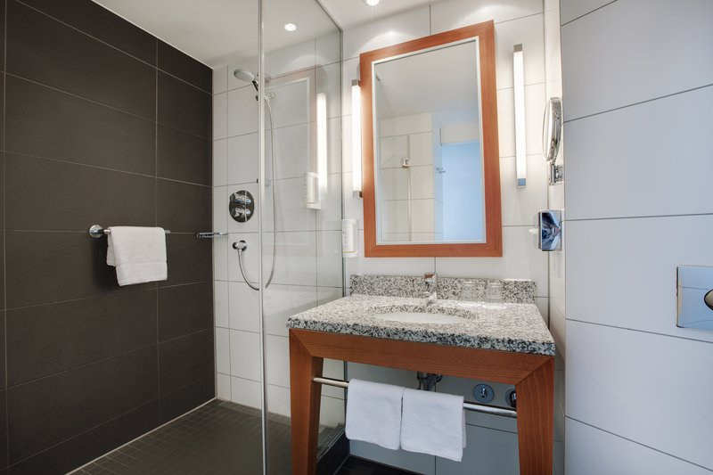 Holiday Inn Berlin Centre Alexanderplatz-Holiday Inn bathroom with washbasin and spacious walk-in shower.<br/>Image from Leonardo