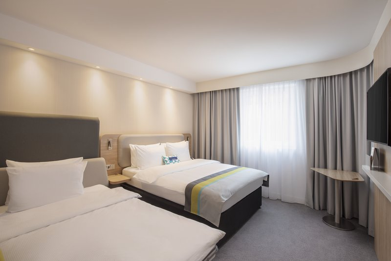 Holiday Inn Express Hamburg - City Hauptbahnhof-A bedroom with a prepared sofa bed, ideal for families.<br/>Image from Leonardo