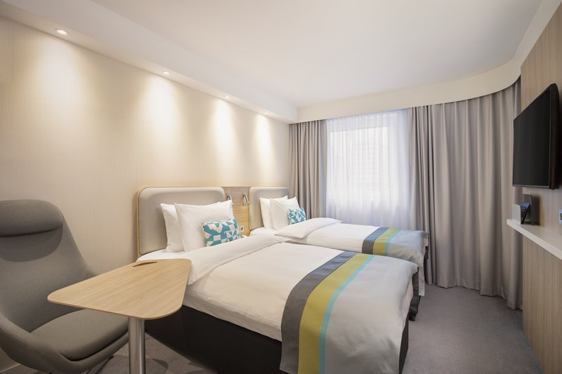 Holiday Inn Express Hamburg - City Hauptbahnhof-Comfortable room with a desk and a chair for work and rest.<br/>Image from Leonardo