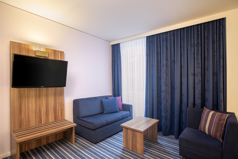 Holiday Inn Express Bremen Airport-Living area in an apartment room with a large TV and twin sofas.<br/>Image from Leonardo