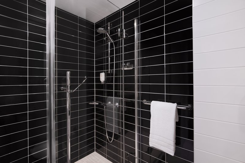 Holiday Inn Express Bremen Airport-A guest bathroom with monochrome design and a power shower.<br/>Image from Leonardo
