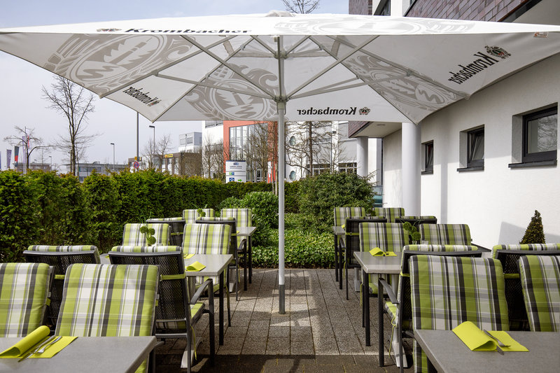 Holiday Inn Express Bremen Airport-Deck chair seating on a shaded patio, ideal for summer drinks.<br/>Image from Leonardo