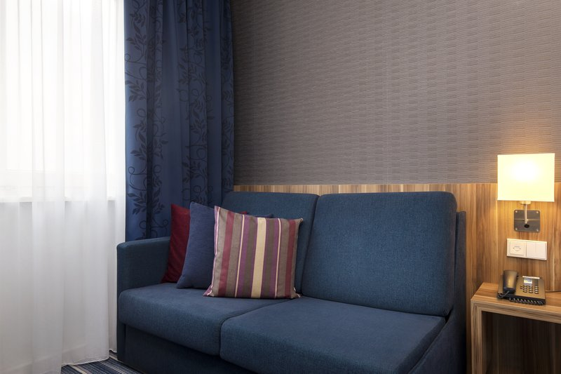 Holiday Inn Express Bremen Airport-A sofa bed in a guest room, ideal for families with kids in tow.<br/>Image from Leonardo