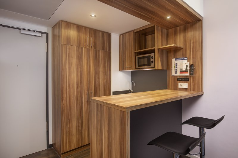 Holiday Inn Express Bremen Airport-Kitchenette with a microwave and fridge in an apartment room.<br/>Image from Leonardo