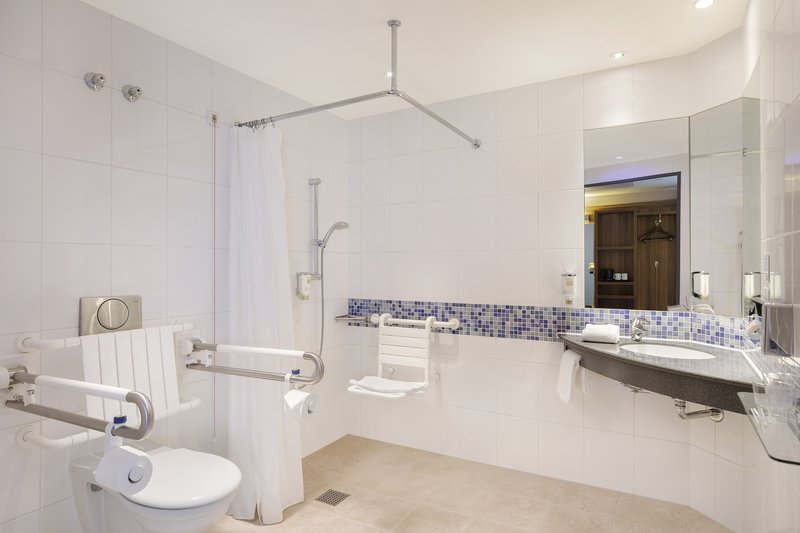 Holiday Inn Express Bremen Airport-An accessible bathroom with safety handrails and a shower chair.<br/>Image from Leonardo