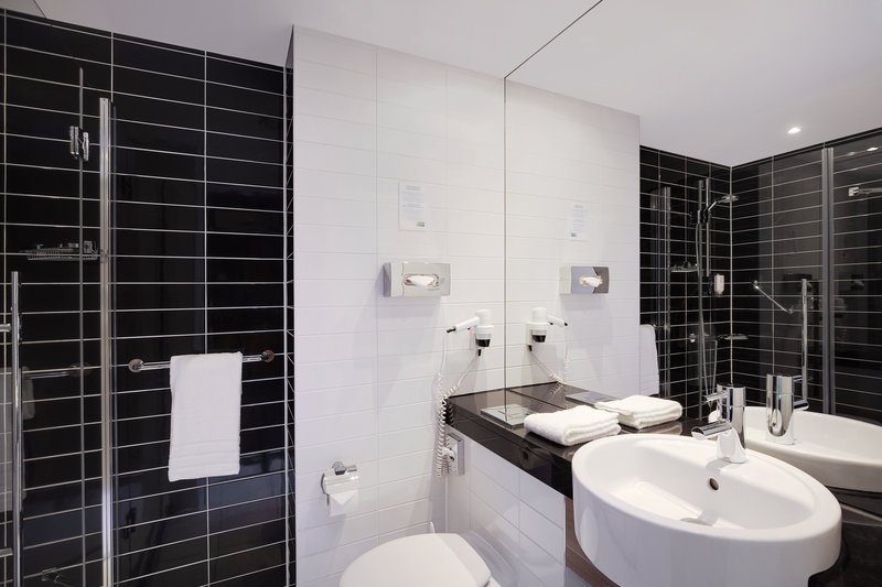 Holiday Inn Express Bremen Airport-A standard bathroom with a hairdryer and walk-in power shower.<br/>Image from Leonardo