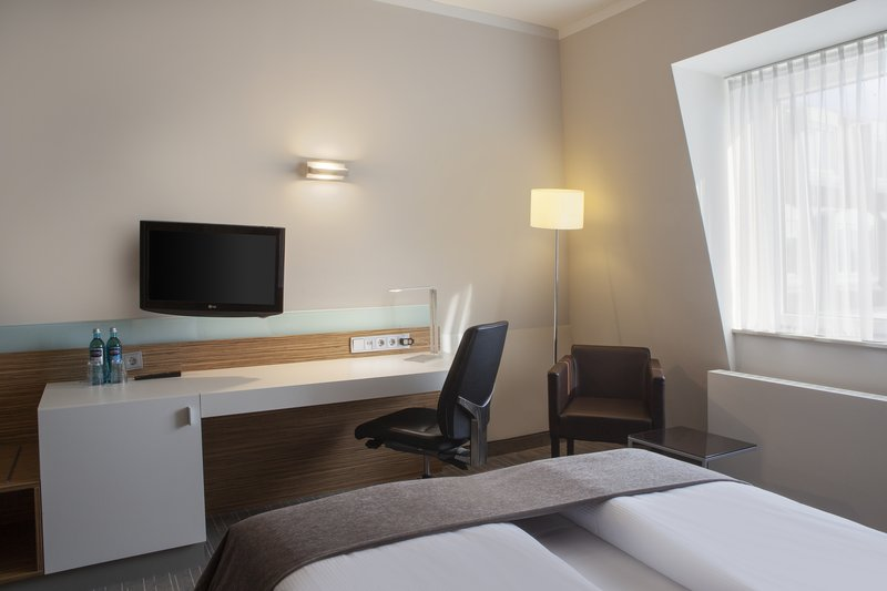 Holiday Inn Leipzig - Gunthersdorf-A comfortable bed, work desk with charging points and a minibar.<br/>Image from Leonardo