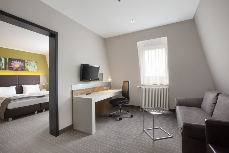 Holiday Inn Leipzig - Gunthersdorf-A suite's spacious living room, perfect for catching up on work.<br/>Image from Leonardo
