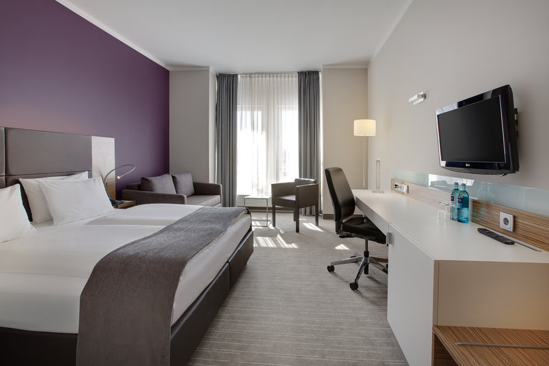 Holiday Inn Leipzig - Gunthersdorf-Large double bed, a sofa and large desk in a spacious family room.<br/>Image from Leonardo
