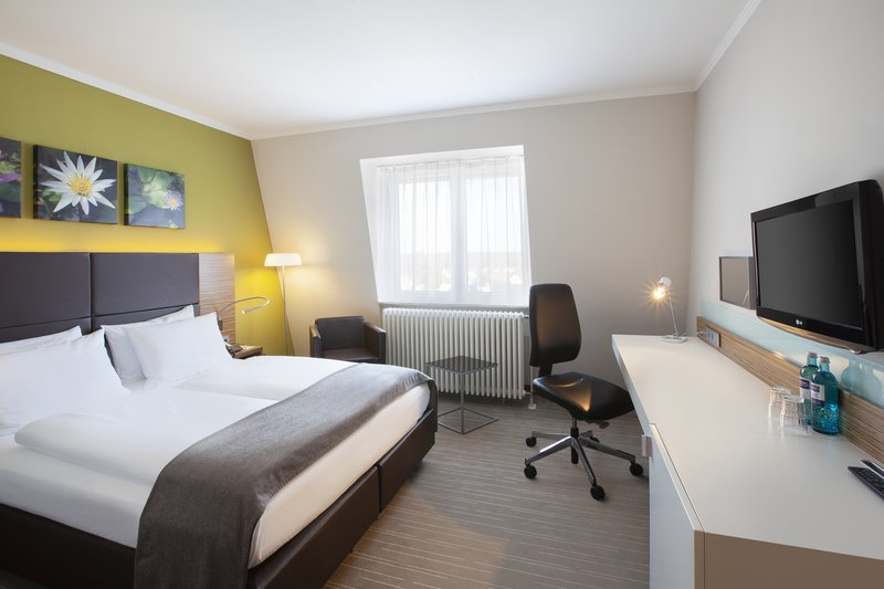 Holiday Inn Leipzig - Gunthersdorf-A guest room with a comfortable bed, large desk and a minibar. <br/>Image from Leonardo