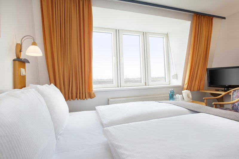 Holiday Inn Leipzig - Gunthersdorf-A well-lit room, with comfortable bedding and a satellite TV.<br/>Image from Leonardo