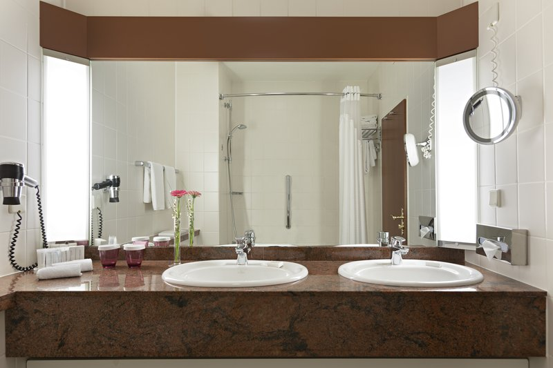 Crowne Plaza Heidelberg City Centre-Upscale bathroom with 2 sinks, hairdryer and a large mirror.<br/>Image from Leonardo