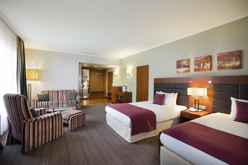 Crowne Plaza Heidelberg City Centre-A spacious room with 2 double beds, plus an armchair and sofa.<br/>Image from Leonardo