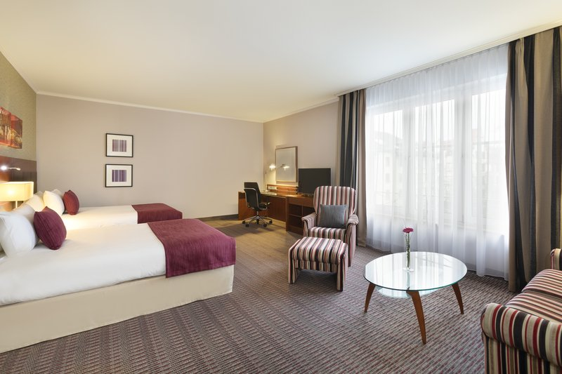 Crowne Plaza Heidelberg City Centre-Natural light-filled room with 2 beds, a work space and armchair.<br/>Image from Leonardo
