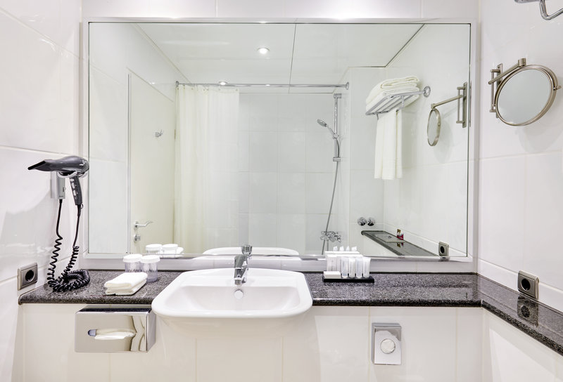Crowne Plaza Hamburg - City Alst-Club room with white-tiled, well-lit bathroom with large mirror.<br/>Image from Leonardo