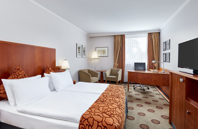 Crowne Plaza Hamburg - City Alst-A club room with queen-size bed, in warm orange and brown tones.<br/>Image from Leonardo