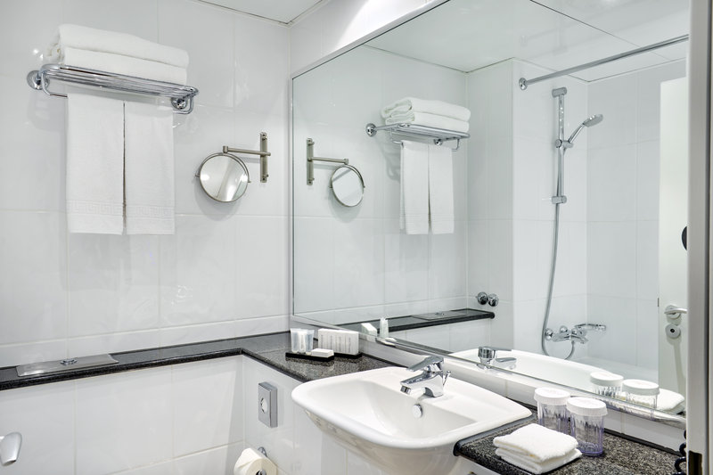 Crowne Plaza Hamburg - City Alst-White-tiled bathroom with a large mirror and walk-in power shower.<br/>Image from Leonardo