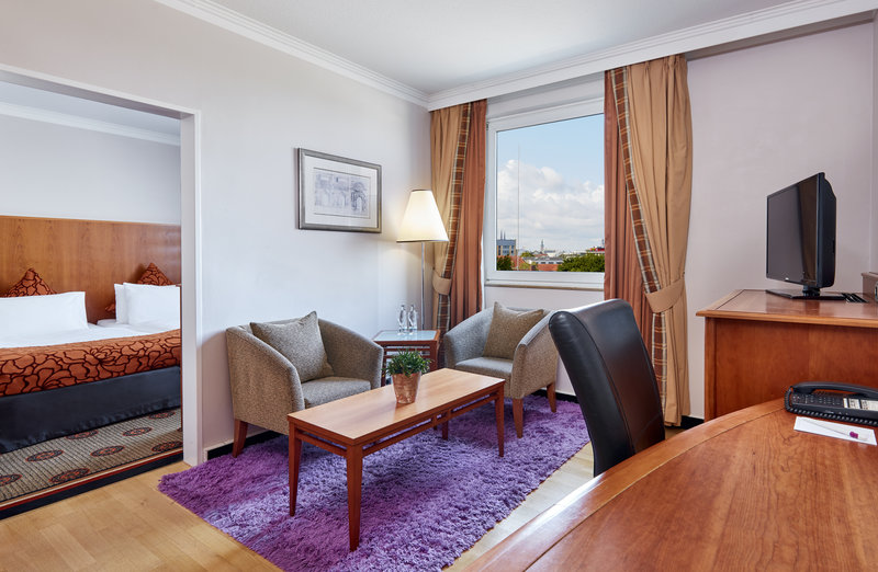 Crowne Plaza Hamburg - City Alst-Living room in a Junior Suite, with a large table and armchairs.<br/>Image from Leonardo