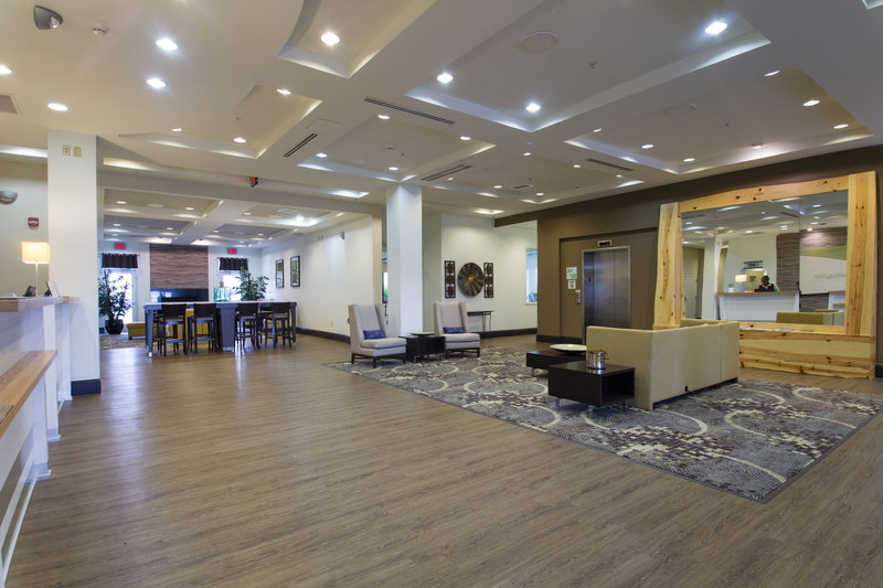 Holiday Inn Hotel & Suites Bloomington - Airport-Modern lobby with community tables including charging ports<br/>Image from Leonardo