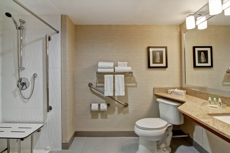 Holiday Inn Oakville Centre-Accessible bathroom with roll in shower and bench<br/>Image from Leonardo
