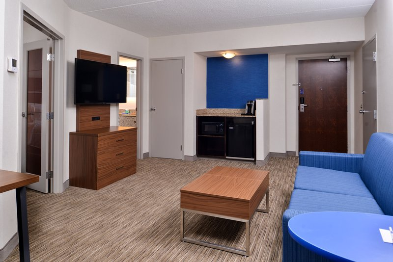 Holiday Inn Express & Suites Buffalo Downtown-King suite livingroom with sofabed, micro/fridge unit, and 49