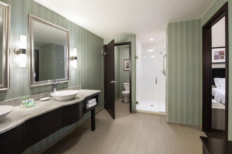 Holiday Inn Saskatoon Downtown-Deluxe guest bathroom with dual vanity sinks and walk in shower<br/>Image from Leonardo