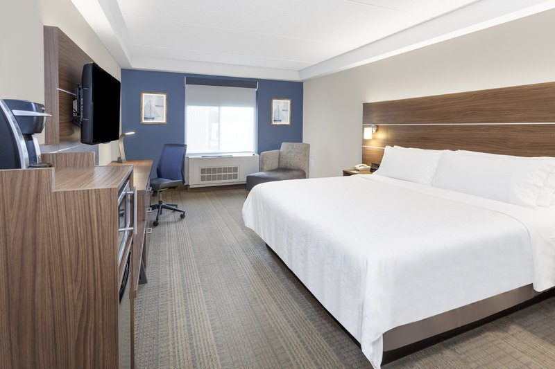 Holiday Inn Express & Suites Long Island-East End-King bed room with Keurig, microwave, & fridge<br/>Image from Leonardo